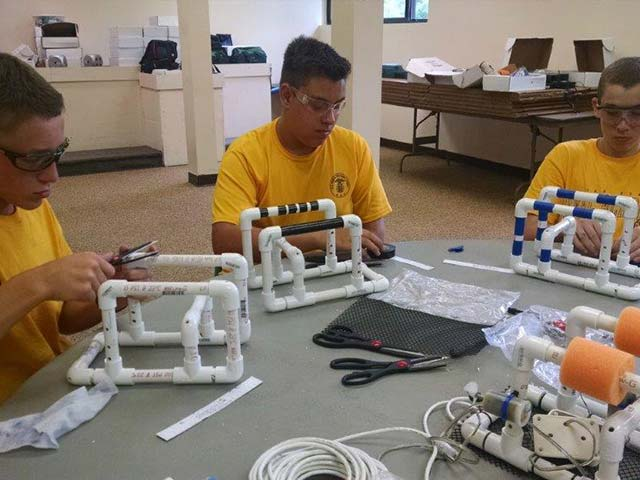Hiram House campers building a project from PVC pipe