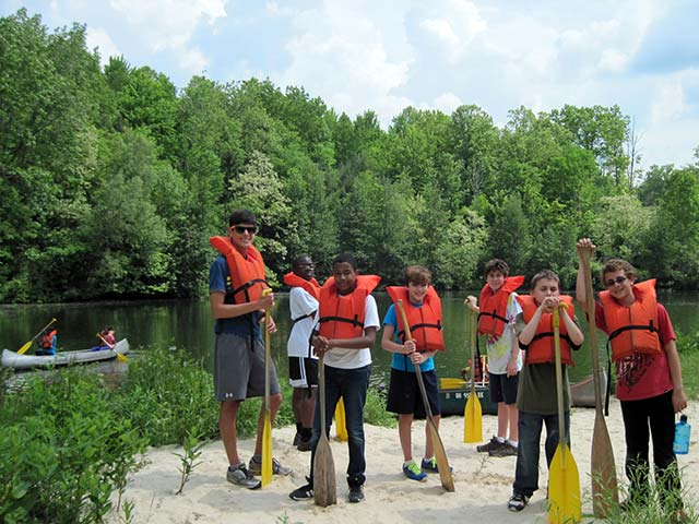 Hiram House campers wearing lifejackets preparing to row in canoes