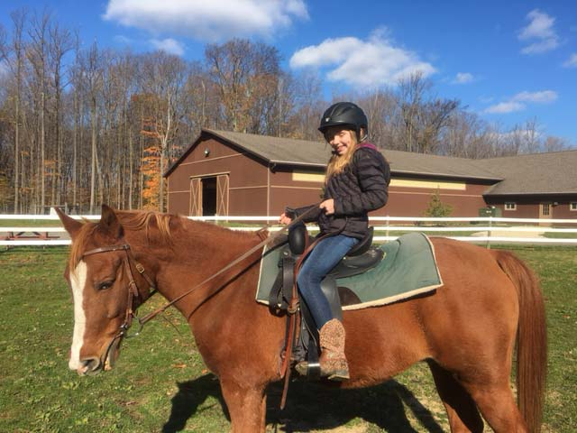 Student riding horse at Hiram House Camp