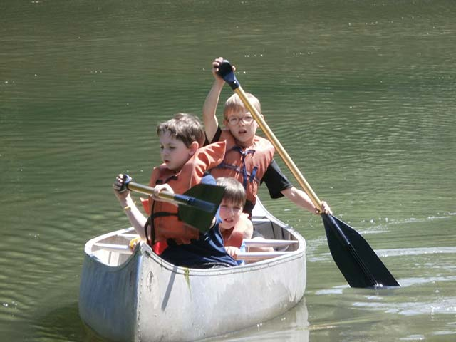 Summer camp students rowing in a canoe